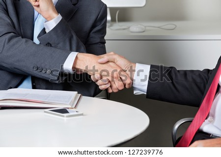 Midsection of two businessmen shaking hands at desk in office - stock photo