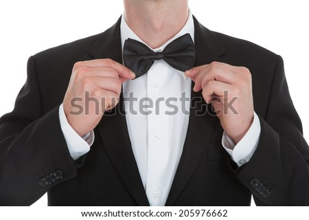 Midsection of waiter adjusting bowtie isolated over white background - stock photo