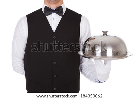 Midsection of waiter holding tray metal cloche lid cover against white background - stock photo