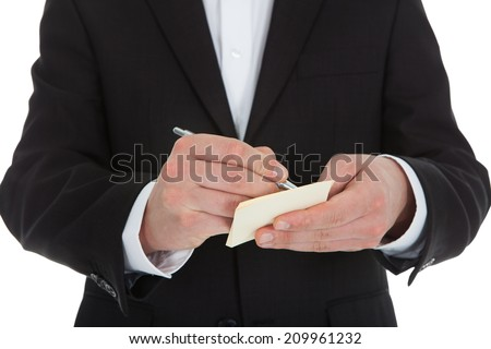 Midsection of waiter writing on notepad isolated over white background