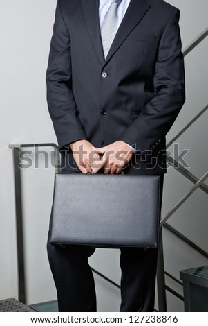 Midsection of young businessman carrying briefcase by steps - stock photo
