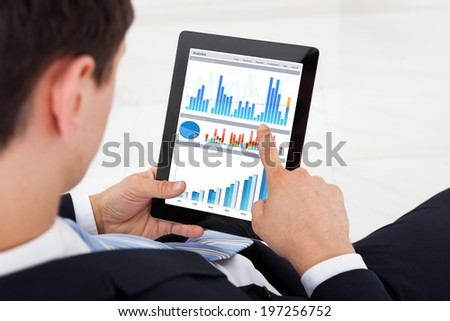 Midsection of young businessman comparing graphs on digital tablet in office