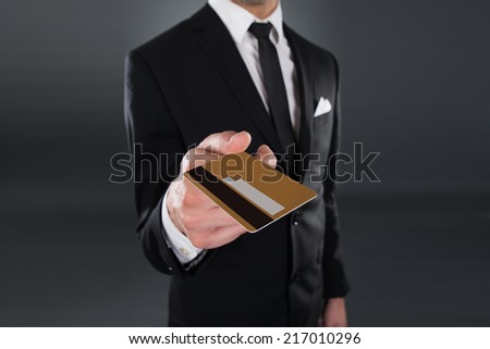 Midsection of young businessman giving credit card against gray background - stock photo