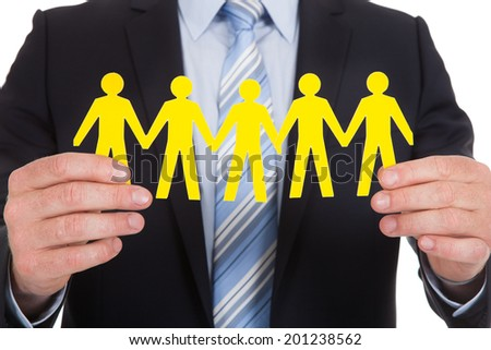 Midsection of young businessman holding team of paper people over white background - stock photo