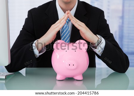 Midsection of young businessman protecting piggy bank at office desk