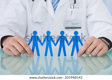 Midsection of young male doctor holding blue paper people chain at desk in clinic - stock photo