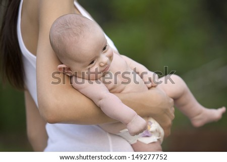 Midsection of young mother carrying baby boy outdoors