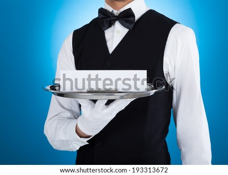 Midsection of young waiter carrying silver tray with blank card over blue background - stock photo