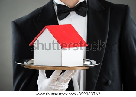 Midsection of young waiter holding house model in tray against gray background - stock photo