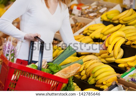 Midsection of young woman choosing bananas in grocery store - stock photo