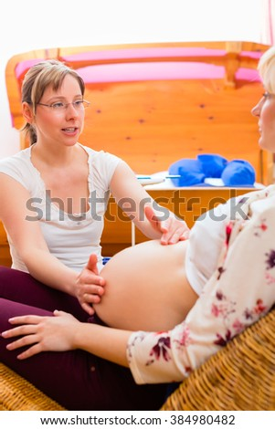 Midwife examining belly of pregnant woman by manual scanning in practice - stock photo