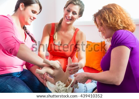 Midwife explaining birth process to pregnant women during antenatal class with anatomic model of pelvic bone - stock photo