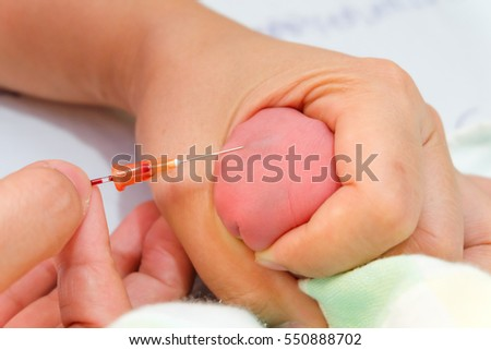 Midwife take blood sample from a newborn during metabolic screening