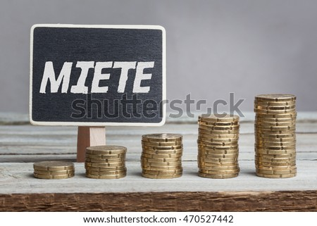 Miete (rent) in German language, white chalk type on black board, Euro money coin stacks of growth on wood table.