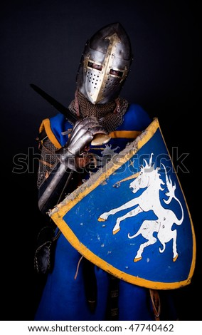 mighty knight holding his sword on shoulders - stock photo