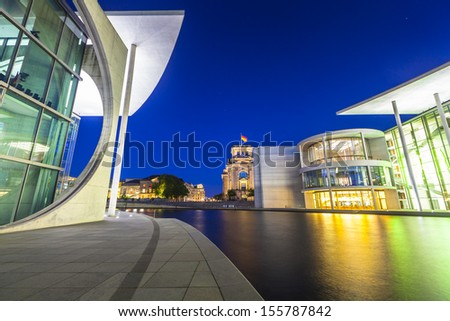 Mighty Reichstag (1894) and government buildings including Bundeskanzleramt the German chancellery illuminated at night and reflected in the river Spree, Berlin, Germany. - stock photo