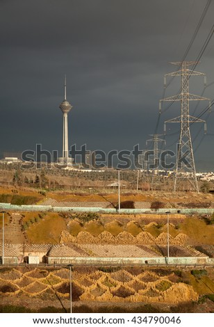 Milad Tower and power transmission lines above hillside, against gray overcast sky of Tehran in autumn. - stock photo