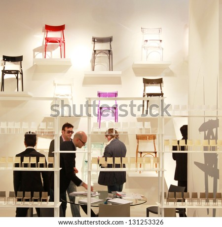 MILAN - APRIL 17: People look at chairs new design in exhibition at Salone del Mobile, international furnishing and home accessories exhibition on April 17, 2012 in Milan, Italy. - stock photo