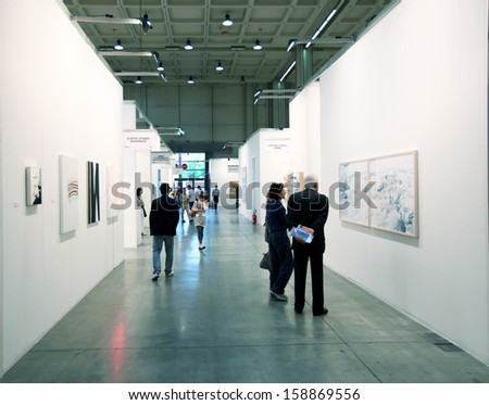 MILAN - APRIL 08: People look at paintings during MiArt, international exhibition of modern and contemporary art on April 08, 2011 in Milan, Italy  - stock photo