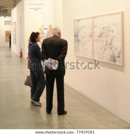 MILAN - APRIL 08: People look at paintings galleries durinfg MiArt, international exhibition of modern and contemporary art on April 08, 2011 in Milan, Italy - stock photo