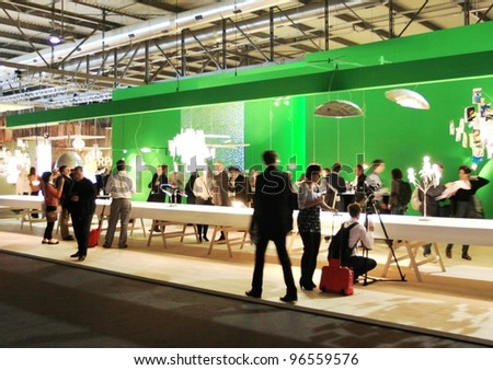 MILAN - APRIL 13: People visit interior lights design exhibition area at Salone del Mobile, international furnishing accessories exhibition on April 13, 2011 in Milan, Italy. - stock photo