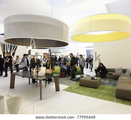 MILAN - APRIL 13: People visit interiors design stands looking for home architecture solutions at Salone del Mobile, international furnishing accessories exhibition on April 13, 2011 in Milan, Italy. - stock photo