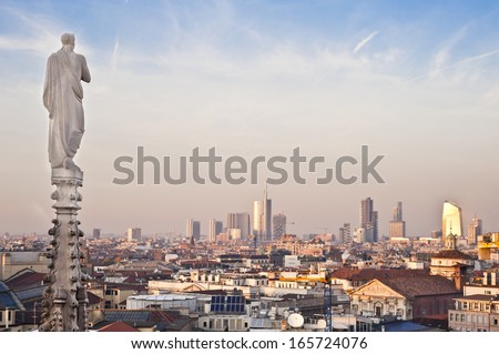 Milan, enew panoramic skyline at sunset. One of the religious statues of Duomo cathedral faces north to the new buildings and skyscrapers of the Garibaldi district. - stock photo