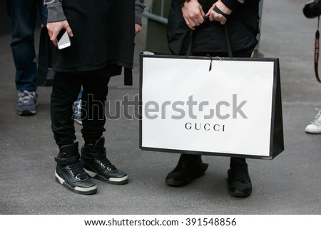 MILAN - FEBRUARY 26: Man poses for photographers holding a big white Gucci shopping bag before Etro and Iceberg fashion show, Milan Fashion Week Day 3 street style on February 26, 2016 in Milan. - stock photo