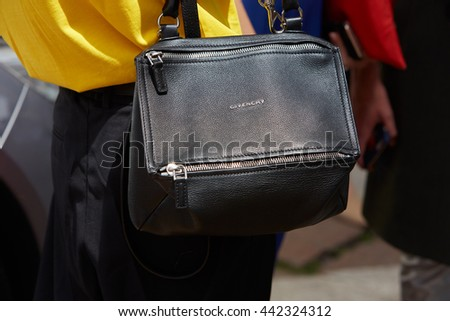 MILAN - FEBRUARY 19: Man poses for photographers with black leather Givenchy bag before Salvatore Ferragamo fashion show, Milan Men's Fashion Week street style on June 19, 2016 in Milan.