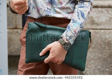 MILAN - FEBRUARY 19: Man poses for photographers with green leather bag and D6G watch before Boglioli fashion show, Milan Men's Fashion Week street style on June 19, 2016 in Milan. - stock photo