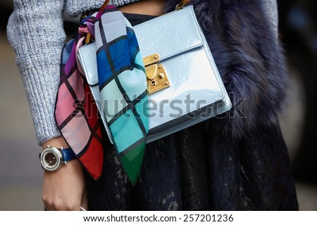 MILAN - FEBRUARY 26: Woman poses for photographers before Anteprima show with blue Louis Vuitton bag Milan Fashion Week Day 2, Fall/Winter 2015/2016 street style on February 26, 2015 in Milan. - stock photo