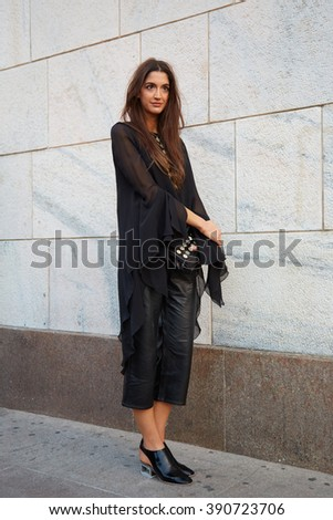 MILAN - FEBRUARY 25: Woman poses for photographers in black clothing before Cristiano Burani fashion show, Milan Fashion Week Day 2 street style on February 25, 2016 in Milan.