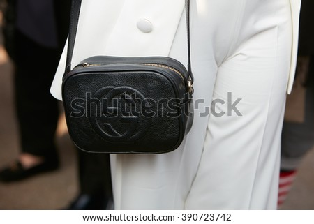 MILAN - FEBRUARY 25: Woman poses for photographers with black leather Gucci bag and white suit before Emilio Pucci fashion show, Milan Fashion Week Day 2 street style on February 25, 2016 in Milan.