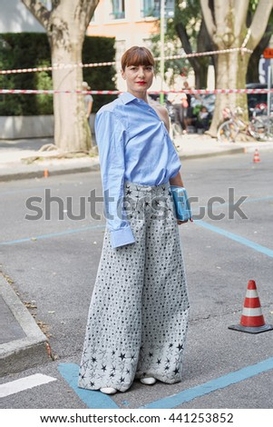 MILAN - FEBRUARY 21: Woman poses for photographers with blue shirt and stars pattern trousers before Giorgio Armani fashion show, Milan Men's Fashion Week street style on June 21st, 2016 in Milan. - stock photo