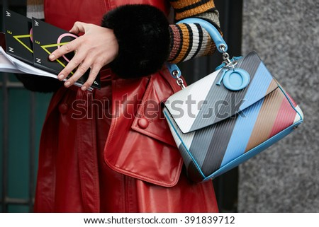 MILAN - FEBRUARY 26: Woman poses for photographers with Dior striped bag and red trench before Emporio Armani fashion show, Milan Fashion Week Day 3 street style on February 26, 2016 in Milan. - stock photo