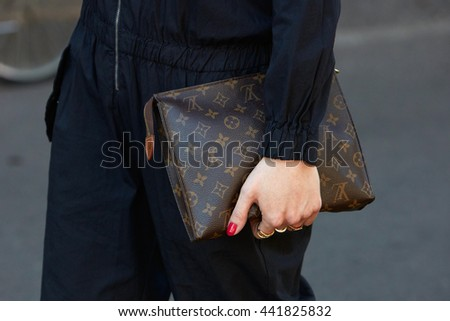 MILAN - FEBRUARY 20: Woman poses for photographers with Louis Vuitton bag before Fendi fashion show, Milan Men's Fashion Week street style on June 20 2016 in Milan.