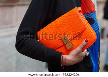 MILAN - FEBRUARY 19: Woman poses for photographers with Orange crocodile leather Celine bag before Missoni fashion show, Milan Men's Fashion Week street style on June 19, 2016 in Milan.