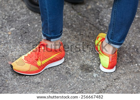 MILAN - FEBRUARY 25: Woman poses for photographers with orange Nike shoes before show Milan Fashion Week Day 1, Fall/Winter 2015/2016 street style day 1, on February 25, 2015 in Milan. - stock photo