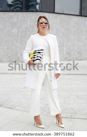 MILAN - FEBRUARY 25: Woman poses for photographers with white jacket and trousers and fur bag before Costume National fashion show, Milan Fashion Week Day 2 street style on February 25, 2016 in Milan. - stock photo