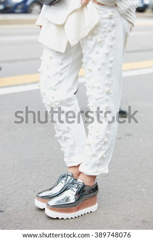 MILAN - FEBRUARY 25: Woman poses for photographers with white pearls decorated trousers and silver shoes before Fendi fashion show, Milan Fashion Week Day 2 street style on February 25, 2016 in Milan.