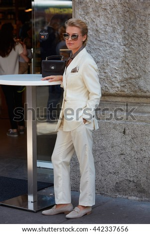 MILAN - FEBRUARY 18: Woman poses for photographers with white suit before Jil Sander fashion show, Milan Men's Fashion Week street style on June 18, 2016 in Milan. - stock photo