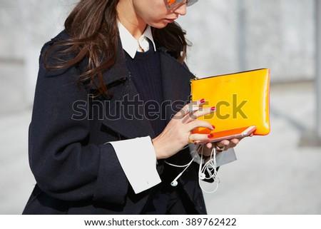 MILAN - FEBRUARY 24: Woman with orange bag checking smartphone before Simonetta Ravizza fashion show, Milan Fashion Week Day 1 street style on February 24, 2016 in Milan. - stock photo