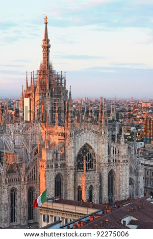 Milan gothic cathedral at dusk as seen by Martini's terrace with the italian flag pictured too - stock photo