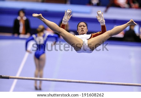 MILAN, ITALY-APRIL 02, 2009: a female gymnast playing high bar exercise, during the European Artistic Gymnastic Championship, in Milan.