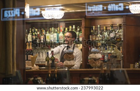 MILAN, ITALY-DECEMBER 02, 2014: barman at work on a traditional milanese bar, seen through the window at night, in Milan. - stock photo