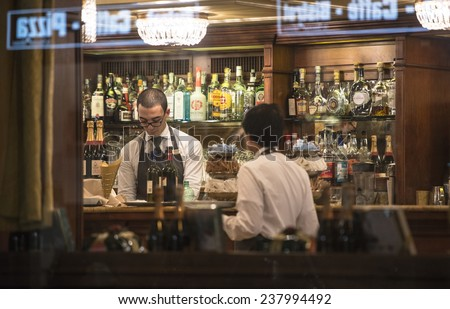 MILAN, ITALY-DECEMBER 02, 2014: barman at work on a traditional milanese bar, seen through the window at night, in Milan.