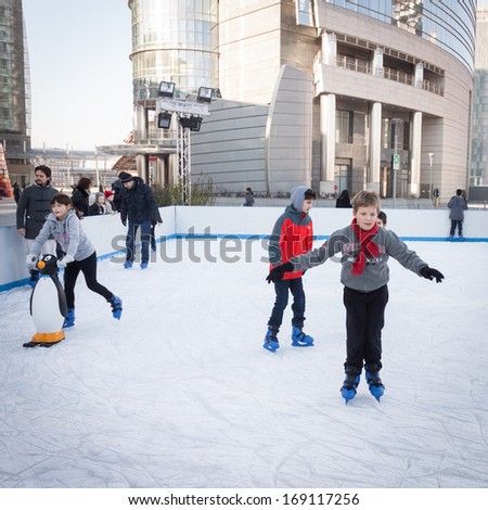 MILAN, ITALY - DECEMBER 27: People have fun skating on a public ice rink built up in the city streets by Municipality during the Christmas period on DECEMBER 27, 2013 in Milan.