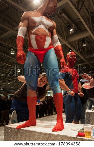 MILAN, ITALY - FEBRUARY 8: Bodybuilders during body painting session at Milano Tattoo Convention, international event dedicated to tattoos, body piercing and body painting on FEBRUARY 8, 2014 in Milan