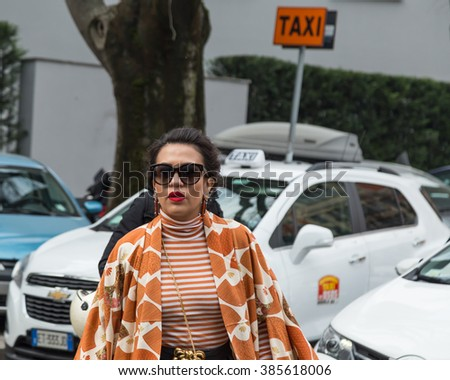 MILAN, ITALY - FEBRUARY 26: Fashionable woman outside Emporio Armani fashion show during Milan Women's Fashion Week on FEBRUARY 26, 2016 in Milan.