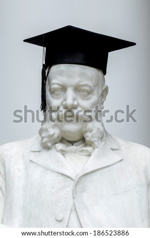 MILAN, ITALY-JANUARY 13, 2012: The statue of Luigi Bocconi, founder of the Bocconi University, wears the graduation cap, during the graduation day, in Milan. - stock photo